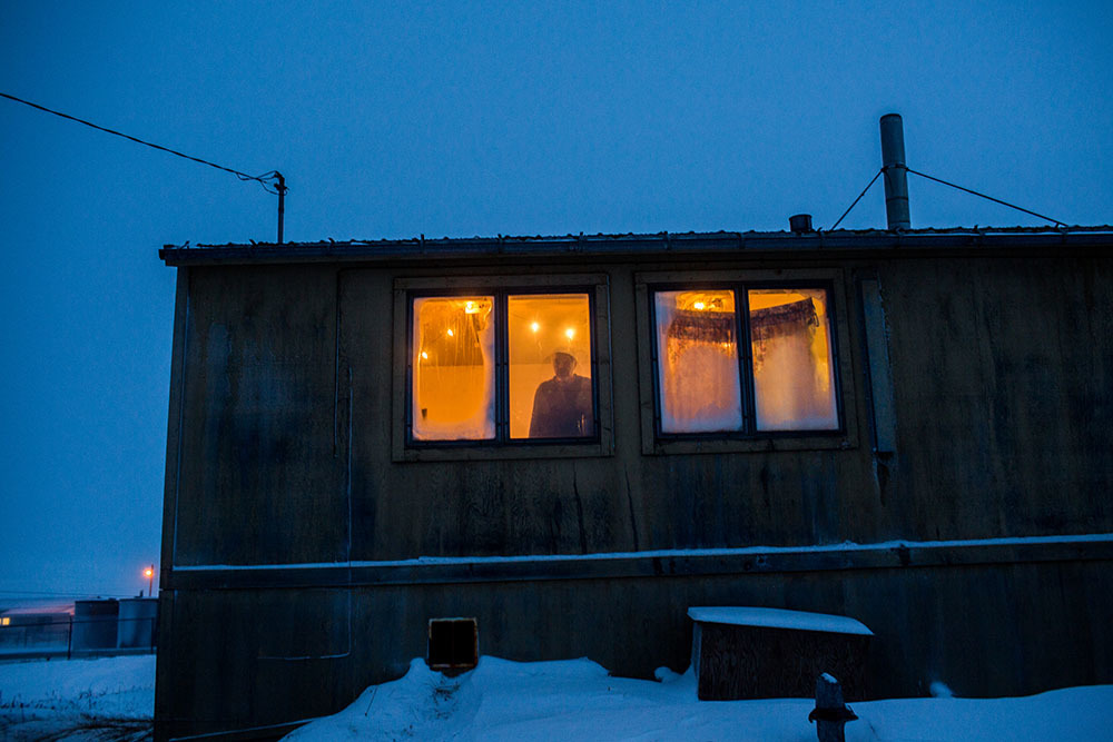 A resident of Shishmaref looking outside through a window of his home. Shishmaref is a barrier island with a population of less than 600 Alaska native Inupiaq people located 30 miles south of the Arctic Circle. The island is threatened by global temperature rises which have disproportionately affected the Arctic. Rising water levels and increased erosion mean that Shishmaref is slowly being absorbed by the surrounding seas and the prognosis is that it will disappear completely over the next two decades.