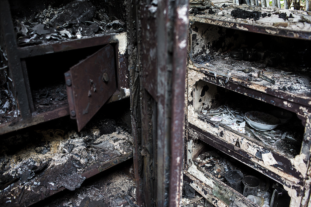 A charred steel cupboard and an utensil rack with the remains of what the fire couldnt consume, in a Bodo home in Tulsibil. Boxes, cupboards and safes were opened up and looted before being torched.