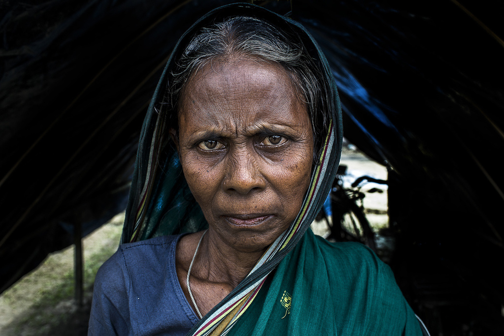 Deep lines form on Rohima Begum's forehead as she complains that the government has been distributing only clothes and medicines, and no utensils. At home or in a tattered tent, the hearth remains her main concern; Bilasipara refugee relief camp.