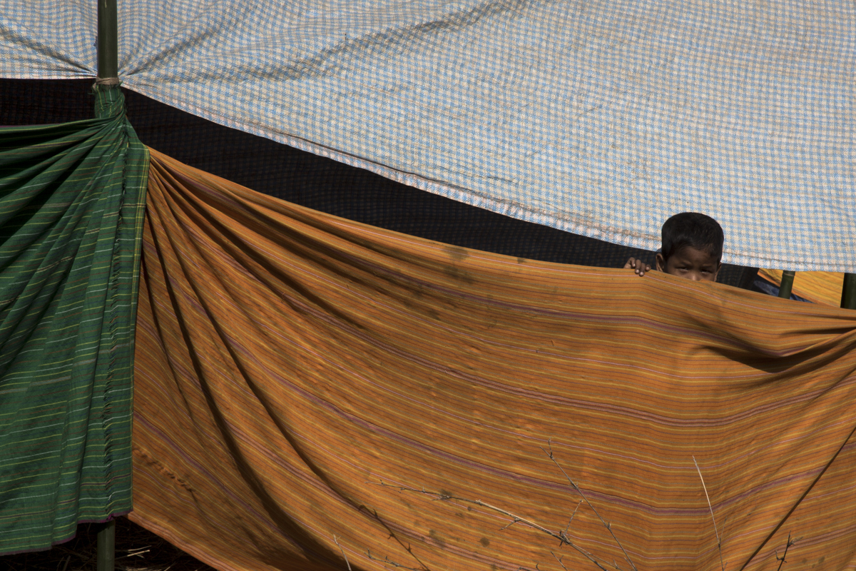 An adivasi boy peeps out of a classroom at a relief camp in Gurfella in Kokrajhar