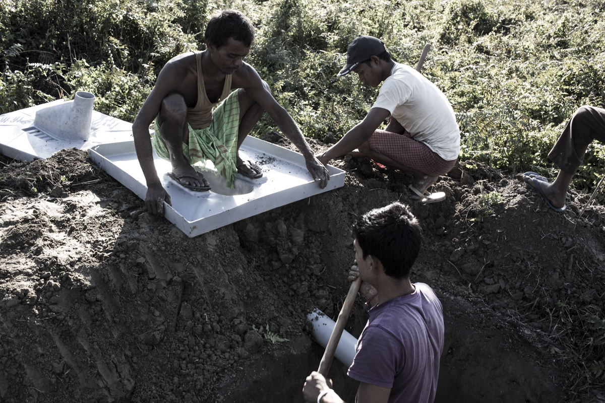 vasis dig a hole to make temporary toilets near Paanbaari relief camp in Kokrajhar. The camp houses over 6,000 people.