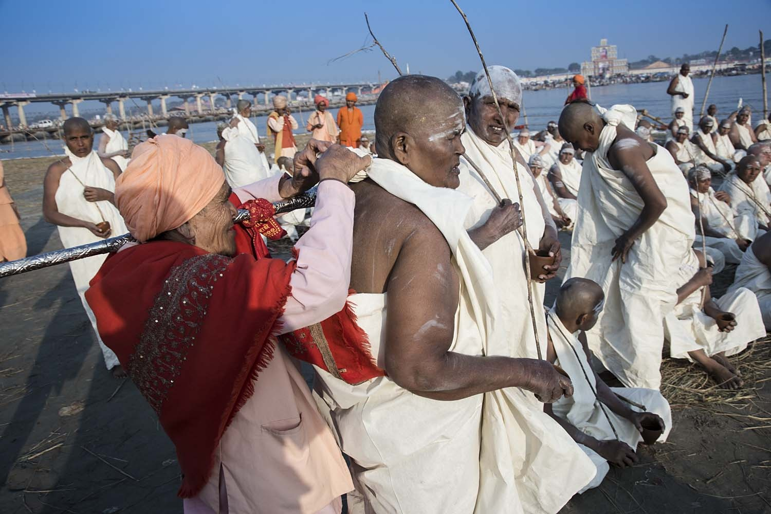 A kotwal (administrator), helps tie the langot to a woman initiate of Juna Akhara by the Ganges.