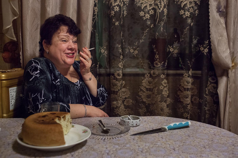 Nadejda, 57, la patiente régulière de l'ancien hôpital numéro 11, se fait plaisir en fumant une cigarette  allégée dans sa cuisine a Moscou, le 16 décembre, 2014.  Elle est malade depuis l'age de 23 ans, mais on ne l'a pas cru au début. Un de symptômes est des crises d'euphorie.