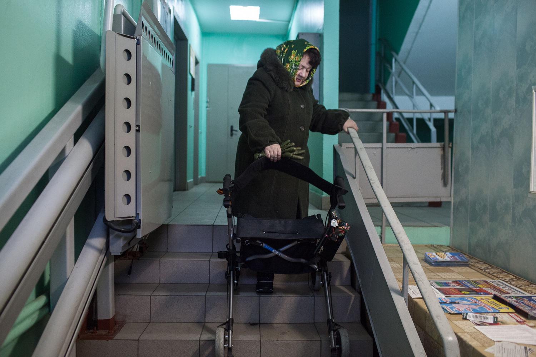 Nadejda, 57, la patiente régulière de l'ancien hôpital numéro 11, va rendre visite a sa copine handicapée, a Moscou, le 19 décembre, 2014.  La plateforme monte-escalier est installée depuis 3 ans, elle n'est pas utilisable car mal installée. La procédure pour l'utiliser est perdue dans la bureaucratie.